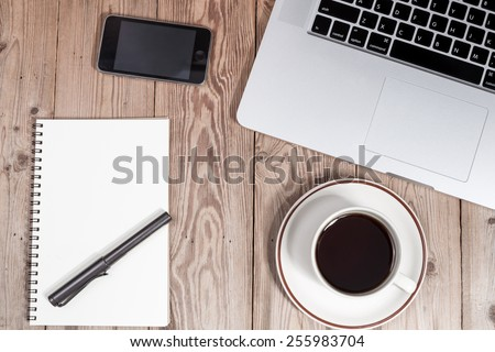 office working desk top view with laptop, smartphone, notepad and coffee cup