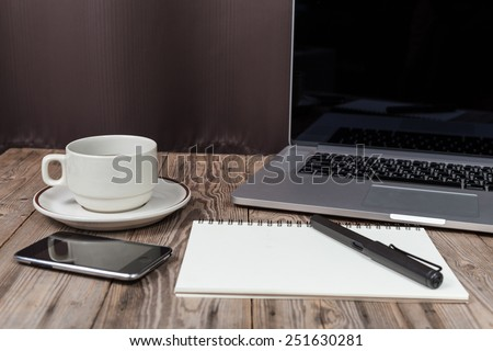 office working desk with laptop, notepad, smartphone and coffee cup