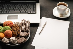 Office workplace. Desk table with laptop computer, cup of coffee and treats. Top view with copy space