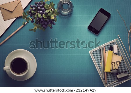 Office workplace,office Equipment and coffee break on blue crepe paper desk,vintage