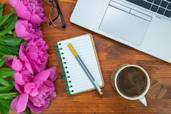 office workplace theme, notepad for writing with a pen, cup of coffee and pink peony flowers at the wooden table background
