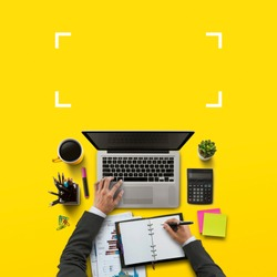 Office workplace with laptop, notebook, hand, office supplies, on yellow background. Solution, business planning, financial analysis, accounting, start up or working flat lay top view concept.