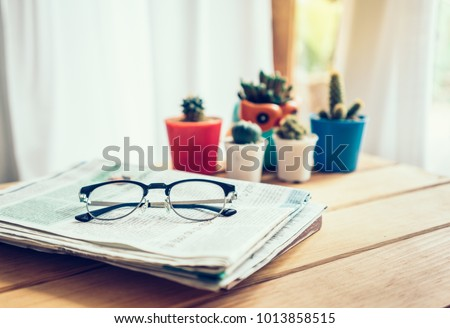 Office workplace with newspaper,glasses and cactus on wood table.