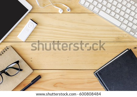 Office workplace with text space, Wooden table with office supplies tablet, desktop computer and book, top view, over light