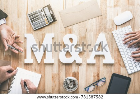Office workstation top view of business people working around M&A, keyboard, calculator, phablet and money on wooden table - merger and acquisition concept