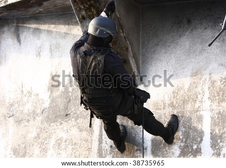 Officer in full tactical gear with weapons climbing down a rope.