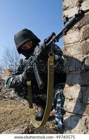 Officer with a rifle sitting in covered position ready to shoot on sight - stock photo