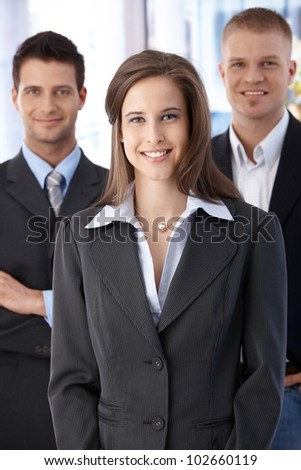 Official business team portrait, confident, smiling businesspeople standing in office.