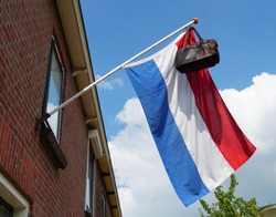 Official Dutch flag with a school bag, a tradition in the Netherlands when a student graduates.