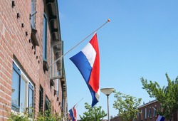 Official flag of the Netherlands attached to a house, hanging half-staff as a symbol of respect.