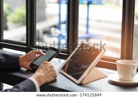 Official professional Business man using multichannel services with internet wifi 5G on smartphone and online tablet in coffee shop.City lifestyle businessman hands working using mobile phone concept