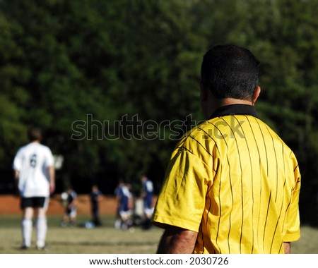 official referee on the sideline of an outdoor soccer game