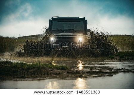 Photo of  Offroad car on bad road. Off road jeep expedition to the villages on mountain road. Mud and water splash in off-road racing. Offroad car
