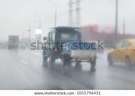 offroad car with a small cargo trailer in the rain on the asphalt wet road. Gray Clouds on the sky . #1055796431