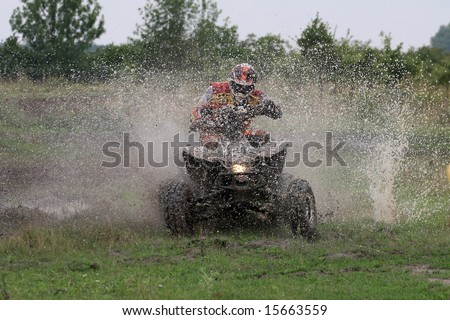 Offroad quad racer getting wet by a big splash.