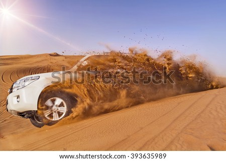 Offroad vehicle bashing through sand dunes in the desert