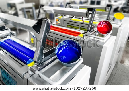 Offset printer press in industry plant. Printing machine print daily newspapers. Detail of four color units, cyan, magenta, yellow and black