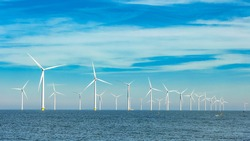 Offshore and onshore windmill park ,Windmill farm green energy at sea,Windmill turbines by the ocean