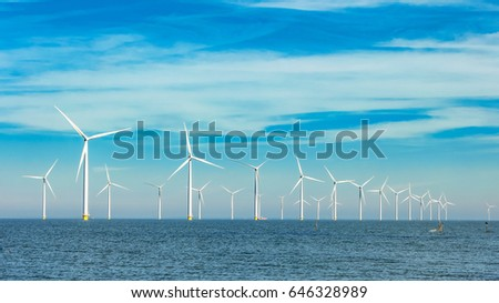Offshore and onshore windmill park ,Windmill farm green energy at sea,Windmill turbines by the ocean Stock photo ©