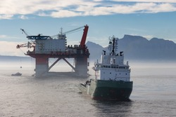 Offshore construction crane rig being towed by ocean going tug