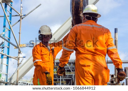 Offshore construction crews preparing the crane block for a heavy lifting of structure frame from a construction barge to oil platform