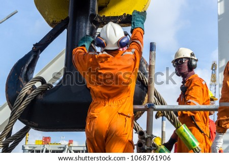 Offshore construction workers handling sling onto crane hook prior to heavy lifting on a construction barge at oil field