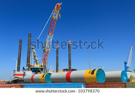 Offshore heavy lift vessel for placing wind turbines in sea, behind parts for wind turbines in a harbor.