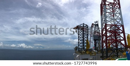 Offshore jack up crane tower tender rig or barge or Derrick of Tender Assisted Drilling Oil Rig (Barge Oil Rig) on The Production Platform During cloudy sky. jack up rig floating exploration. panorama