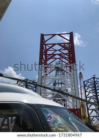 Offshore jack up crane tower tender rig or barge or Derrick of Tender Assisted Drilling Oil Rig (Barge Oil Rig) on The Production Platform During cloudy sky. jack up rig are floating exploration.