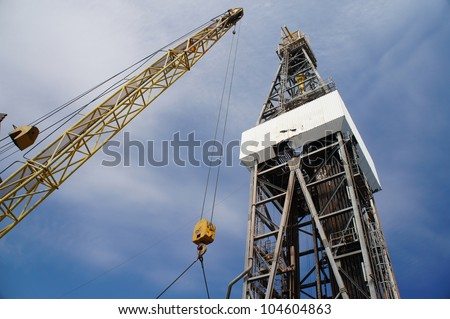 Offshore Jack Up Oil Rig (Drilling Rig) and Rig Crane Working on Sunny Day