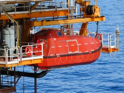 Offshore Life boat or survival craft at muster station of oil and gas drilling rig. Lifeboat in offshore, rescue boat or rescue team in the sea.