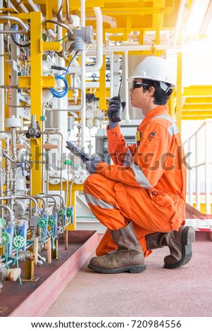 Offshore oil and gas business, production operator using hand held radio and talk with central control room to report abnormal condition of gases process, Maintenance and service activity. #720984556