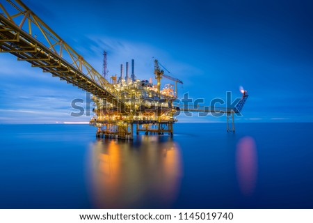 Offshore oil and gas central processing platform in sun set which produce raw gas, crude and hydrocarbon then sent to onshore refine, petrochemical industry. Power and energy business.