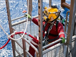 Offshore oil and gas diver in his diving cage during recovery back to deck after completing an underwater task on a newly installed jacket.