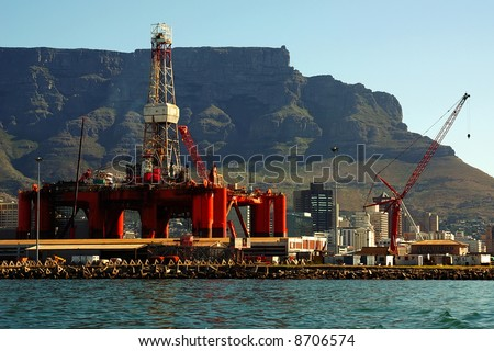 offshore oil extraction rig in bay into a big city near mountains. cape town, south africa