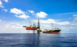 Offshore oil field area viewed with FPSO ship and drilling rig on platform