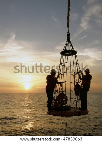 Offshore oil field workers being lowered from the rig to a boat below