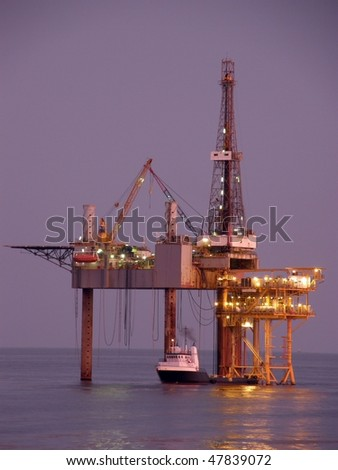 Offshore oil platform, drilling rig, and supply boat at twilight