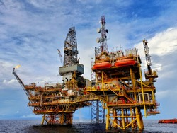 Offshore oil platform for production of oil and gas. Jack up rig to drill new well in sarawak sea during clear sunny day.