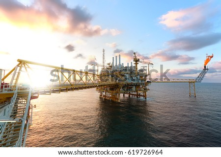 Offshore oil  platform in sunset or sunrise time. Construction of production process in the sea. Power energy of the world.