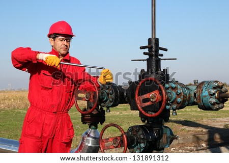 Offshore Oil Rig Operator.Oil worker in safety gear with hand tool working on oil rig equipment.