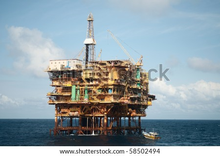 offshore oil rig with fishing boat connected to it.  Coast of Brazil - stock photo