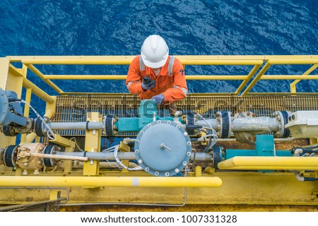 Offshore oil rig worker checking parameter of coriolis digital flow transmitter meter, instrument and electrical service of oil and gas energy business, A man using radio at petroleum industry.