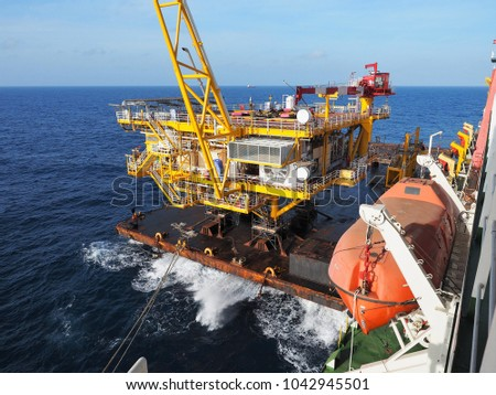 Offshore platform topside is secured on material barge alongside derrick lay barge in the morning.