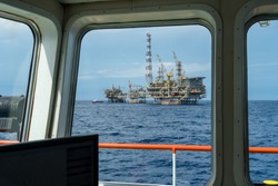 Offshore production platform viewed from an anchor handling tug boat bridge with a fast crew boat approaching for crew change