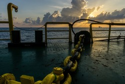 Offshore scenery of an oil field onboard a construction work barge with anchor windlass chain during a sunset