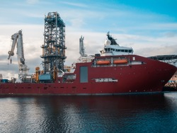 Offshore seismic vessel or ship for searching oil in port. Oil Rig and crane on background