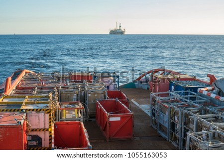 offshore supply boat with containers and tanks onboard delivers cargo to oil rig platform. Calm sea. Dp supplier job. oil and gas research and mining indusrty