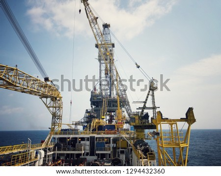 Offshore tender rig crane tower tender rig or barge or Derrick of Tender Assisted Drilling Oil Rig (Barge Oil Rig) on The Production Platform During cloudy sky