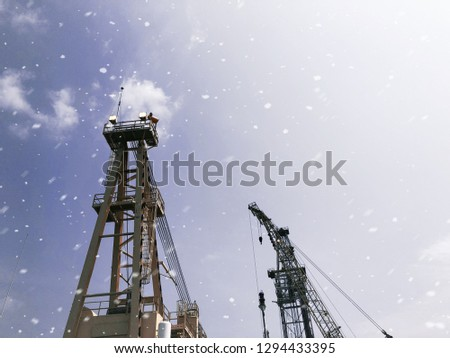 Offshore tender rig crane tower tender rig or barge or Derrick of Tender Assisted Drilling Oil Rig (Barge Oil Rig) on The Production Platform During cloudy sky and white snow